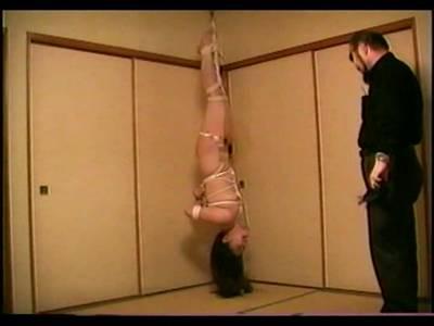 Die Tussi wird vom asiatischen Zuchtmeister mit den Füßen nach oben gefesselt